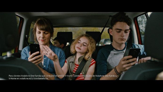 One, la niña que personifica el servicio, entre dos miembros de la familia que protagoniza el anuncio.